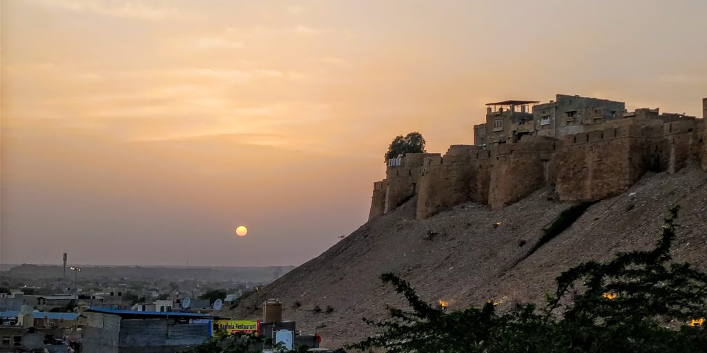 The sun setting behind Jaisalmer Fort after another day of backpacking Jaisalmer